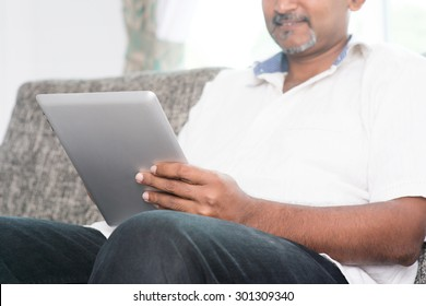 Modern technology concept. Mature Indian man using wireless touch screen digital tablet pc at home. Asian people living lifestyle indoors.