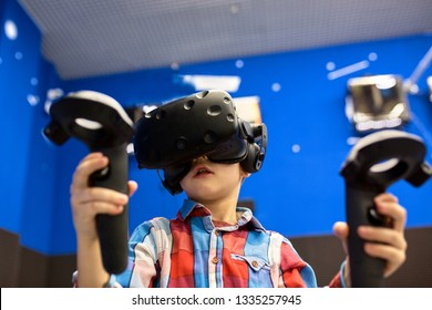 modern technology, gaming and people concept - boy in virtual reality headset or 3d glasses playing videogame at game centre