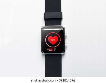 modern technology, health care, object and media concept - close up of black smart watch with heart-rate on screen