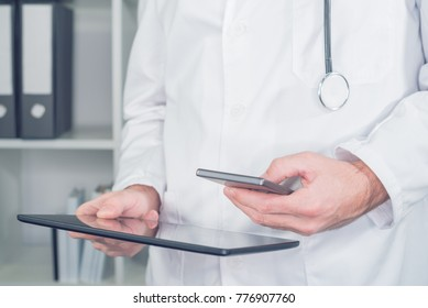 Modern technology in healthcare and medicine. Male doctor using smartphone and digital tablet computer in office.