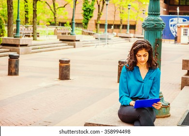 Modern technology in our daily life. East Indian American student, wearing blue shirt, sitting by light pole on campus in New York, looking down, reading tablet computer. Instagram filtered look.