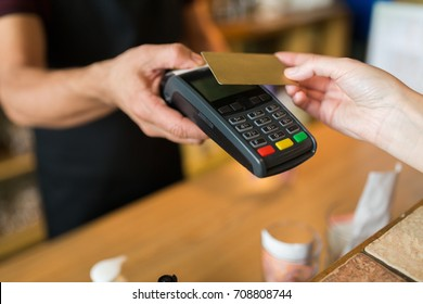 modern technology and people concept - man or bartender with payment terminal and customer hand with credit card at bar of coffee shop