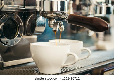 Modern technology for the perfect drink. Brewing coffee with espresso machine. Espresso making with portafilter. Coffee being brewed in coffeehouse. Coffee cups. Small cups to serve hot coffee.