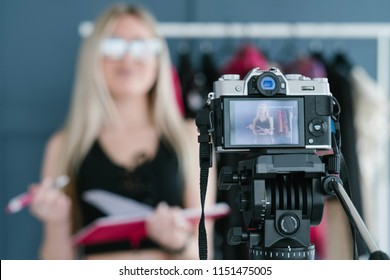 modern technology for photo and video shooting. camera on tripod. blogger equipment and tools. image of a woman conducting a review on screen.