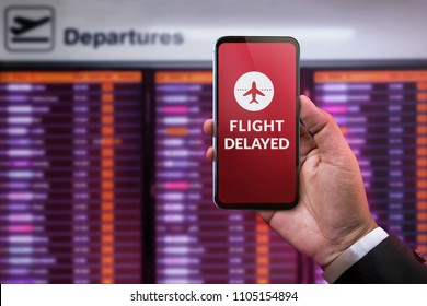 Modern Technology in Travel Concept. Flight Delayed on Smartphone Screen. Businessman using Mobile Phone in front of Departures Board to Re-Checked Flight Information in Airport