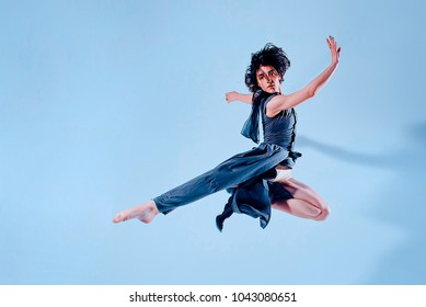 Modern teen contemporary dancer poses in front of the studio background. Toned image. Like a doll view. motion picture in the jump view