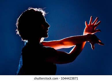 Modern teen contemporary dancer poses in front of the studio background. Toned image. Like a doll view. portrait with the hands