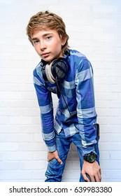 Modern teenage boy enjoys the music in headphones. Studio shot. Youth culture.