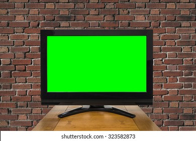 Modern television with chroma key green screen and red brick wall.
