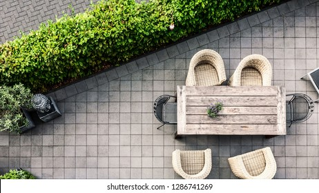 Modern terrace patio with table and rattan chairs surrounded by lush greenery, high angle view. Relaxing area