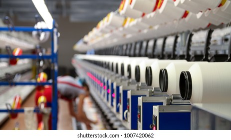 Modern Textile Plant. Female Textile Worker at Work.  Automated Yarn Spinning Machines. Row of automated machines for yarn manufacturing.