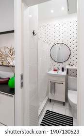 Modern tiled bright white-black bathroom and toilet in a small studio apartment. Interior view with cabinet and sink on it, round mirror, shower, toilet and carpet on the floor from the hallway