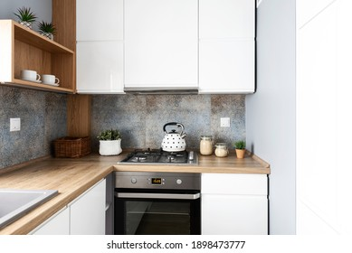 Modern tiles pattern in small bright kitchen in apartment. White furniture cabinets and wooden counter top with oven and kettle. Scandinavian design. Nobody.