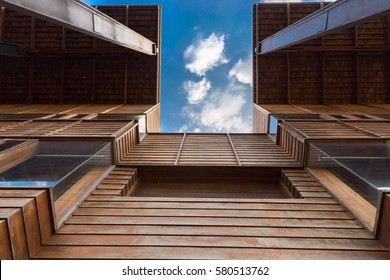 Modern timber clad building with an upward view to a cloudy blue sky