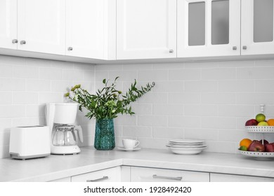 Modern toaster, coffeemaker and dishware on countertop in kitchen