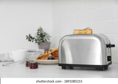Modern toaster with slices of bread and different jams  on white table in kitchen