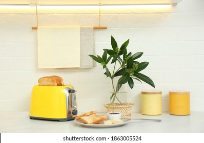 Modern toaster and tasty breakfast on counter in kitchen