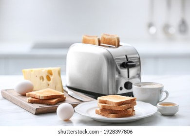 Modern toaster and tasty breakfast on white marble table in kitchen