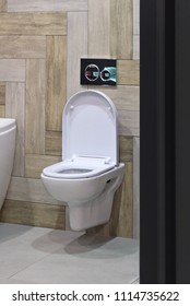 Modern toilet bowl inside contemporary bathroom interior with beige tiles