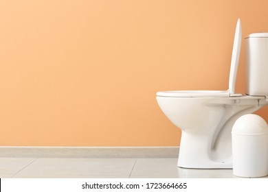 Modern toilet bowl near color wall in restroom