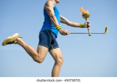 Modern torchbearer athlete running with sport torch in motion blur with his smartphone on the end of a selfie stick