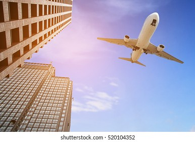 Modern tower with airplane flying over city