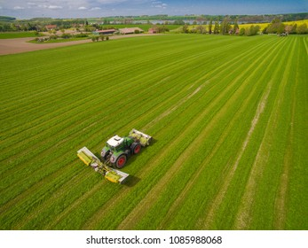 modern tractor mowing a green fresh grass field - Aerial view