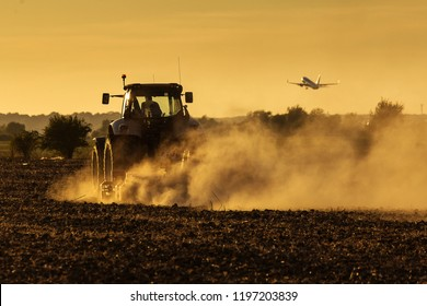 Modern tractor plowing at the sunset with lot of dust in background and with a plane taking off