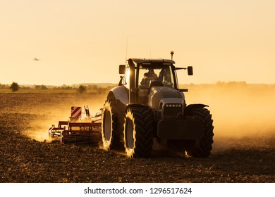Modern tractor plowing at the sunset with lot of dust in background