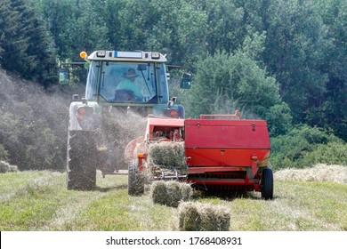 Un tracteur moderne utilise un balancier de quarante ans pour transformer le foin sec en balles de foin. Grâce à sa solide construction, l'ancienne presse fonctionne encore de manière fiable.