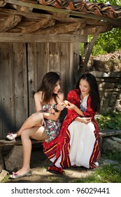 Modern and traditional folklore women sharing an apple in a village in Bulgaria