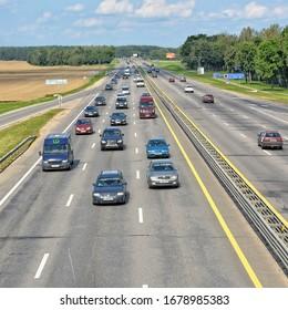 Modern traffic. Cars on a motorway. Road infrastructure. Congestion. Many vehicles. Urban landscape. Commuter transport. Trip. Belarus, Minsk – July 3, 2016