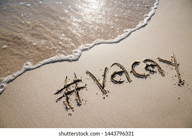 "Modern travel message for the beach with a social media-friendly hashtag written with the word ""vacay"" in smooth sand with incoming wave"