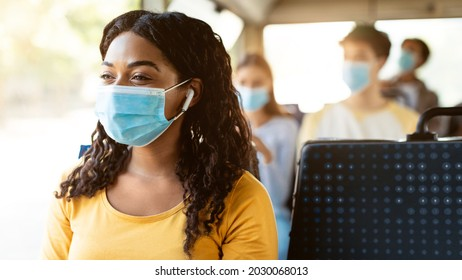 Modern Travels. Portrait of happy smiling black female passenger in medical face mask traveling on public transit, listening to music in wireless earphones looking away at window, thinking, panorama