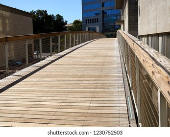 Modern trendy design bridge made of metal and wood in a city town urban landscape