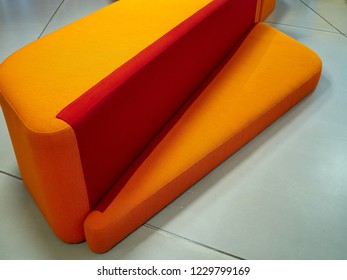 Modern trendy Scandinavian style sofa in bright strong orange and red colors
