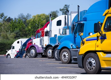 Modern trucks of various colors and models are involved for the transportation of different kinds of commercial goods are in row on a truck stop in anticipation of the continuation of working flights