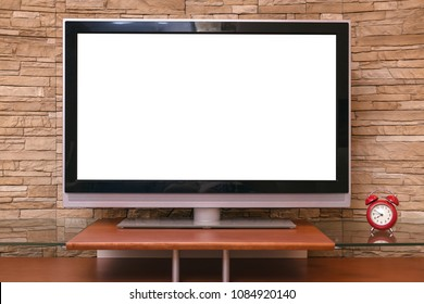 Modern TV set with empty blank screen and red alarm clock on the table on the decorative brick wall background.