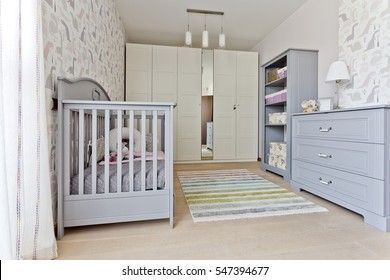 Modern universal nursery with grey babcy cot, built-in wadrobe and commode