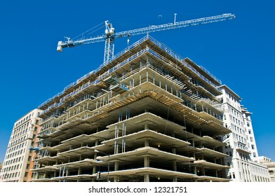 modern urban building under construction with a crane and blue sky