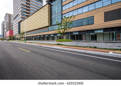 The modern urban commercial building and asphalt road