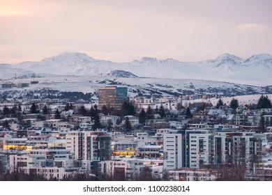 Modern urban development in Reykjavik, Iceland in front of snow covered mountains and fjords.