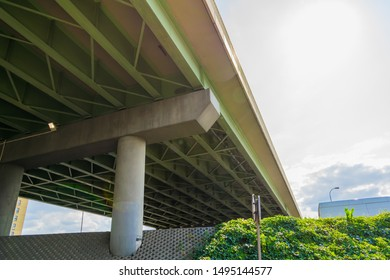 Modern urban elements. Overpass road,  green space. Steel trussing of overpass construction. Lime green, new. Under the bridge view.