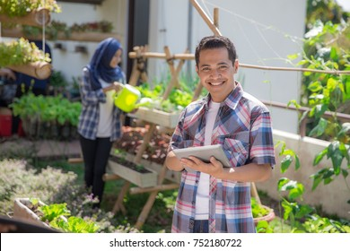 modern urban farming concept. young male standing with tablet pc