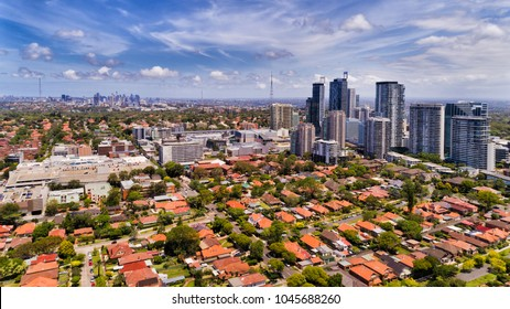 Modern urban high-rise towers of Chatswood suburb in Sydney surrounded by residential low houses with red roofs and local streets in view of distant city CBD.