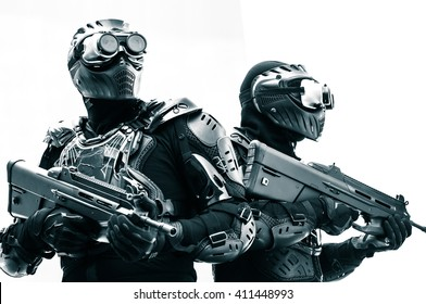 Modern urban soldiers of special elite commando units posing in special black tactical uniform with machine guns with white background