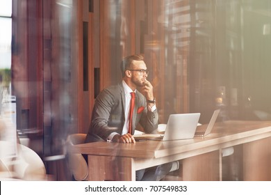 Modern user. Professional confident handsome businessman sitting at the table and using his laptop while working in the office