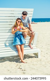 Modern Vacation. Wearing glasses, barefoot, dressing in summer outfits, girl and guy relying on each other on a wooden structure, reading messages on mobile phones. Young couple on the beach.