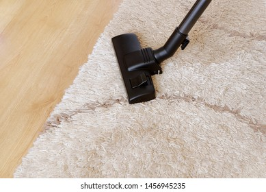 Modern vacuum cleaner on a beige carpet wooden parquet. Concept of housekeeping, housework, vacuuming the carpet. Copy space for text, from above.