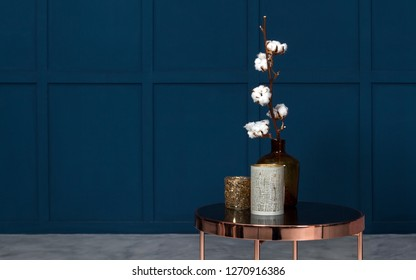 Modern Vases on metal copper side table in room with blue wooden walls